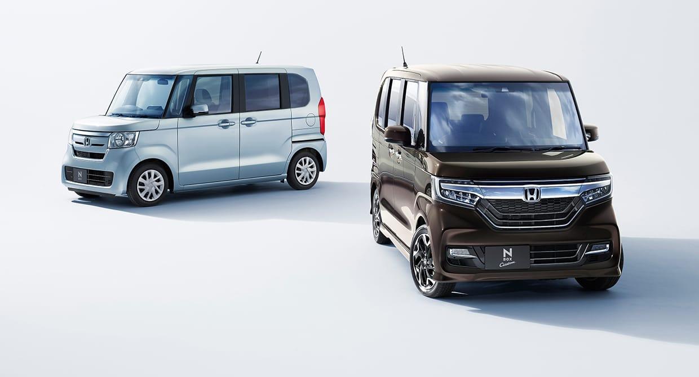 [左] N-BOX G・EX Honda SENSING (FF) ボディーカラーはモーニングミストブルー・メタリック ディーラーオプション(N-BOX専用 8インチ プレミアム インターナビ VXU-207NBi)装着車、[右] N-BOX Custom G・EX ターボ Honda SENSING (FF) ボディーカラーはプレミアムグラマラスブロンズ・パール ディーラーオプション(N-BOX専用 8インチ プレミアム インターナビ VXU-207NBi)装着車